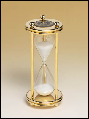 555 - Glass crystal sand timer with polished brass finish case and columns with black brass plate.